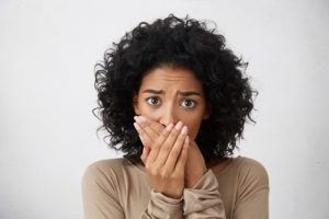 embarrassed woman covers her mouth